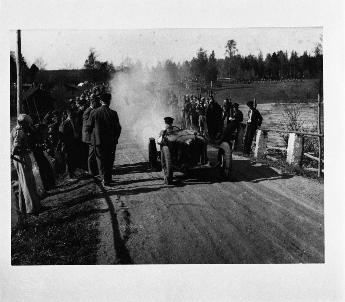 Reproduktion Röfors Man som kör en bil/traktor med mycket rök bakom. Publiken står i vägkanten och tittar på. publik vid vägen