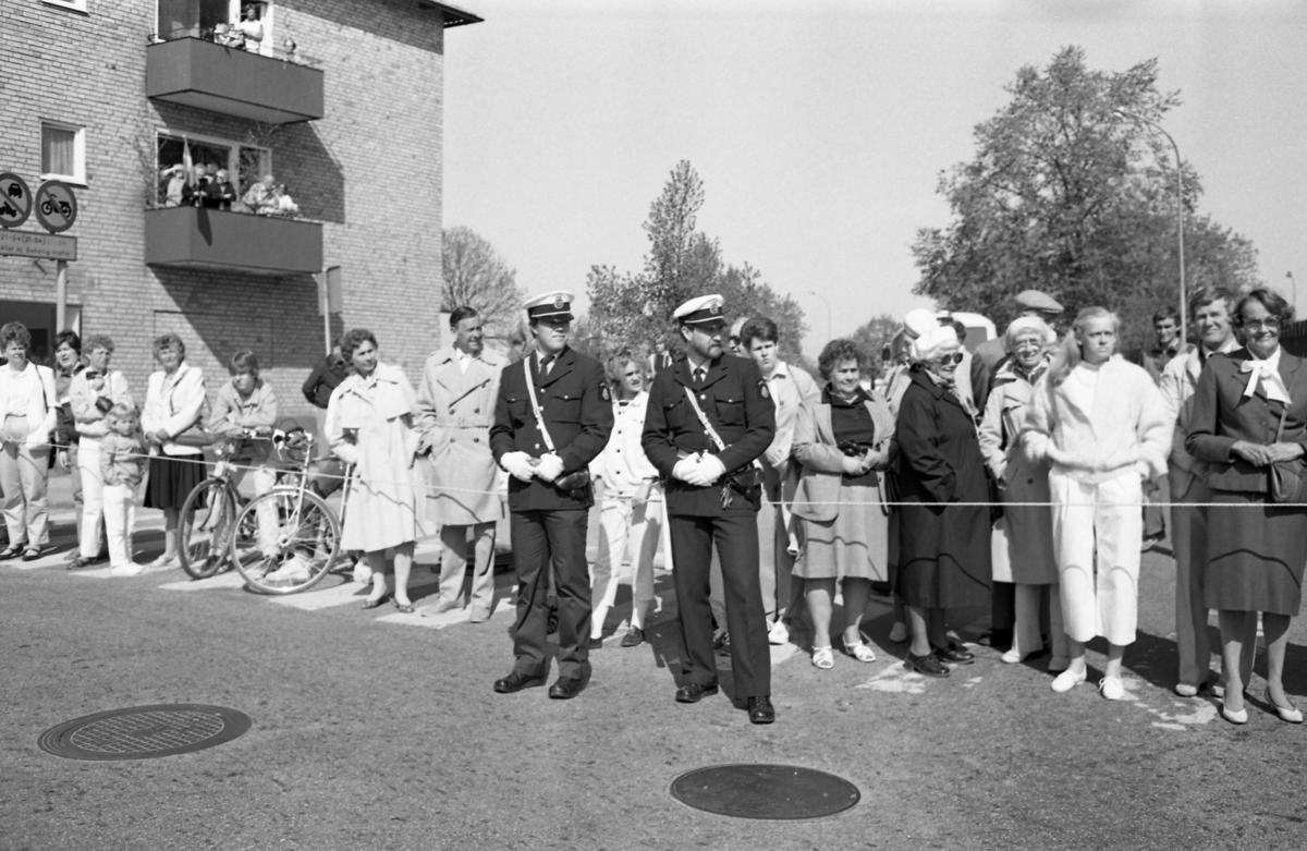 Riksdagsjubileet 1985. I Arboga firas 550-årsminnet av Sveriges första riksdag. Människor står bakom avspärrningen och väntar på kungaparet och kända riksdagspolitiker. Längst till höger står Ing-Britt Rydh, ägarinna av Ryds damekipering på Smedjegatan. Två uniformsklädda poliser håller allt under uppsikt. Bilden är tagen i korsningen Nygatan - Centrumleden.