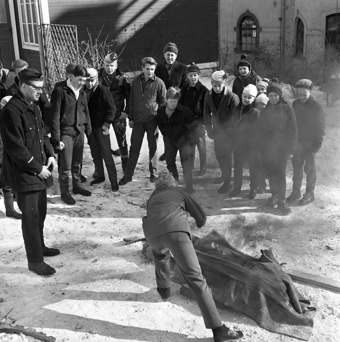 Skolelever övar brandsläckning. Brandman Håkan Waern instruerar. Det är snö och kallt. Många av pojkarna har mössa på sig. De håller till bakom brandstationen på Strandvägen.