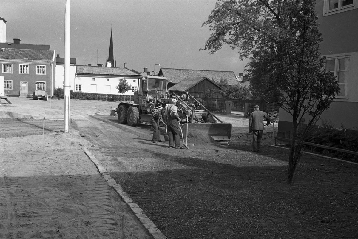 Engelbrektskolans gård asfalteras. I bakgrunden ses tornet på Heliga Trefaldighetskyrkan.