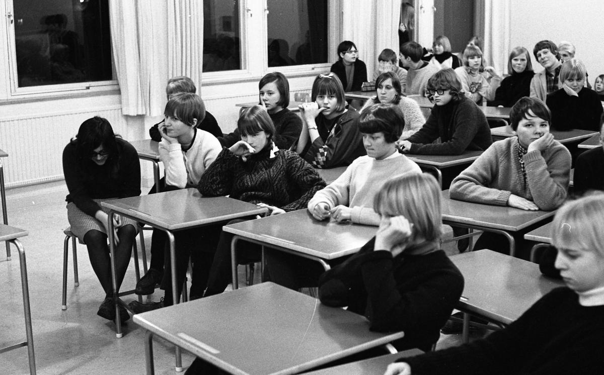 Elever från ett par årskurser är samlade för att lyssna på musik. De sitter vid bänkar i ett klassrum. Flickan längst till vänster är Agneta Östman (gift Karlsson), bredvid henne, i ljus tröja, Christina Hagen. Bakom Christina sitter Anna-Greta Sjöberg. Bredvid henne, Käthe Tiborn. Ovanför Käthes huvud syns Agneta Darlsson. Bakom Käthe sitter Chatarina von Kartachew. Pojken som tittar på fotografen, och har hakan i handen, heter Ove Norman.