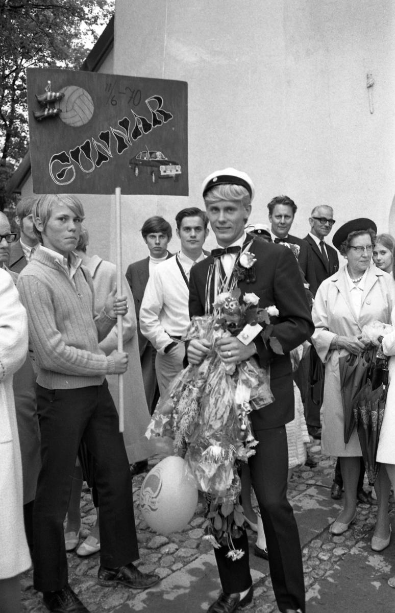 Studentdag! Gunnar Franzén iklädd studentmössa och mängder av blombuketter om halsen. Hans bror, Thomas Franzén, håller i studentplakatet. Den blonde mannen, bakom Thomas, är Lennart Strömbom. Efter kyrkväggen står, från vänster: Per Björsson, Arne Larsson, Ingwald Franzén och Annie Jakobsson.