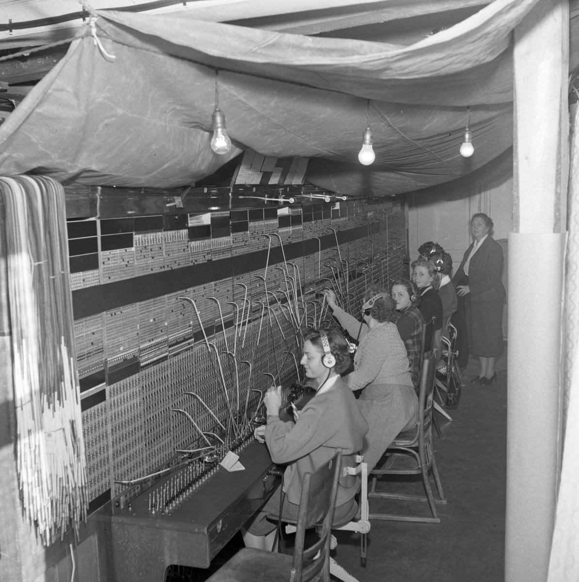 Kvinnorna arbetar vidare i telefonväxeln trots branden på Televerket på Nygatan. En presenning är uppspänd över växelbordet och personalen. Nakna glödlampor hänger från taket. Läs om Telefonen i Arboga och branden på Televerket 1956 i Arboga Minnes årsbok 1993.