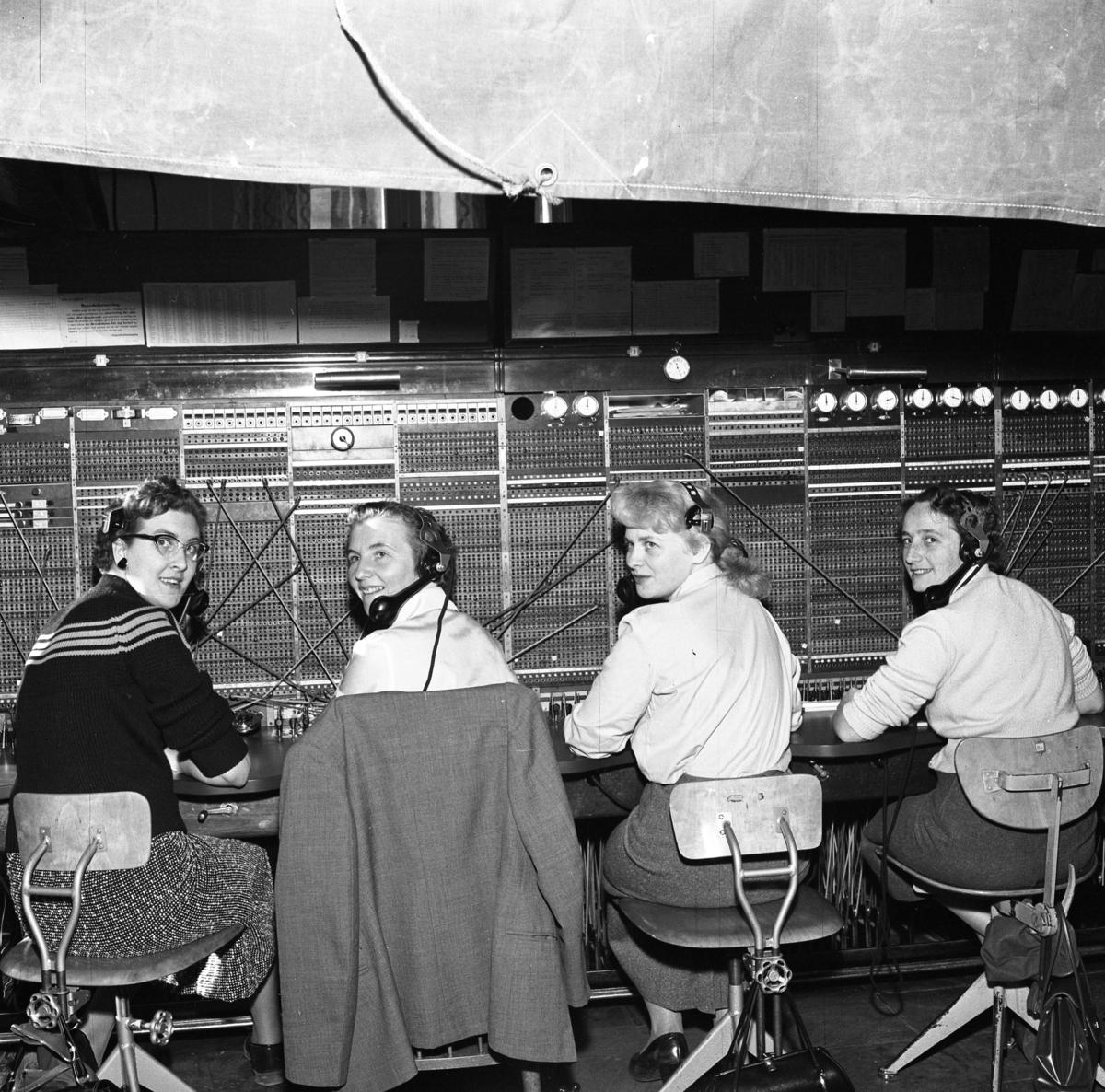 Det har brunnit i Televerkets hus på Nygatan. Trots brandskadorna fortsätter kvinnorna sitt arbete vid växelborden. Här sitter fyra växeltelefonister med var sin telefonlur vid örat. En presenning är spänd över arbetsplatsen. Läs om Telefonen i Arboga och branden på Televerket 1956 i Arboga Minnes årsbok 1993.
