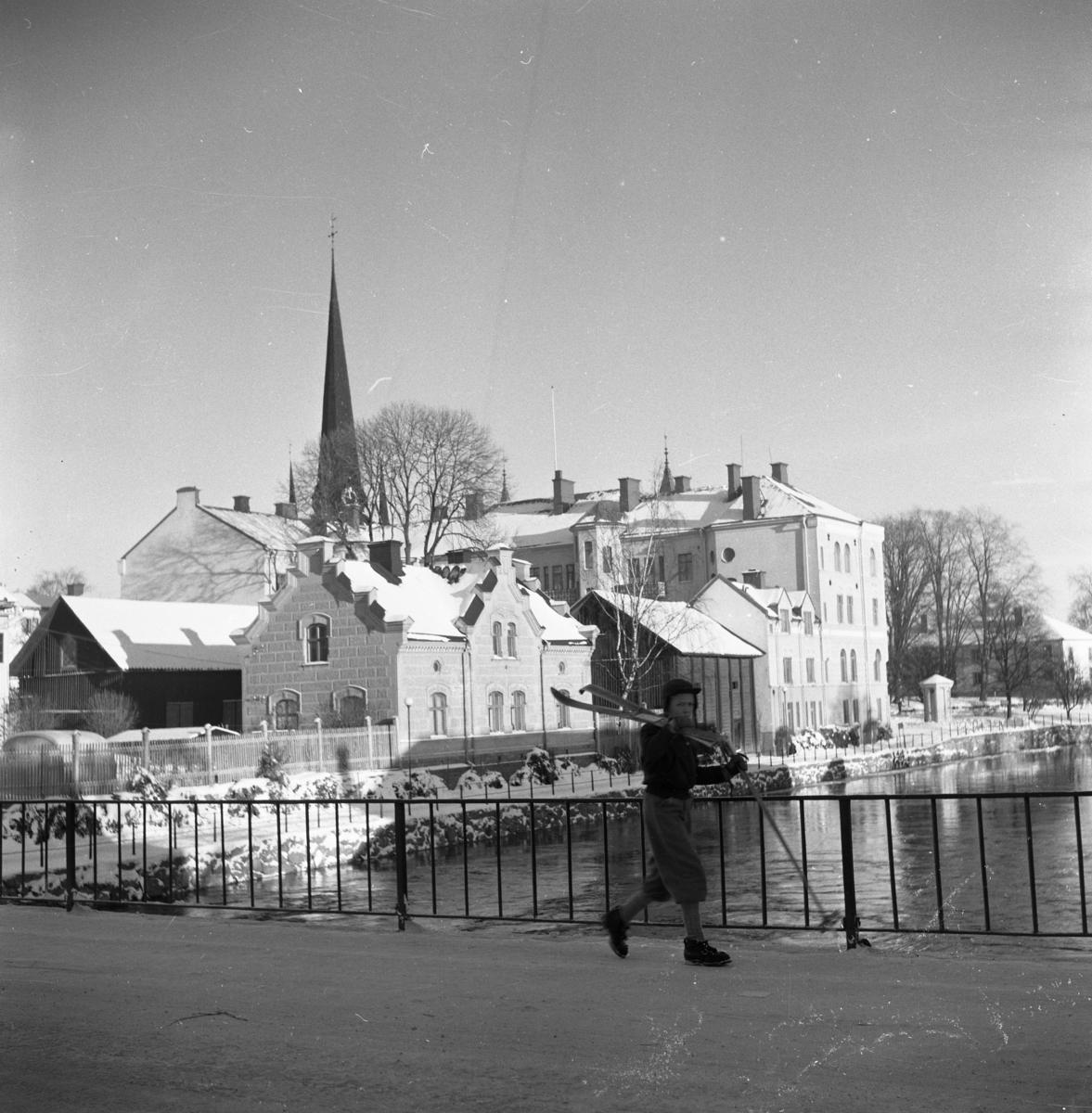 """Vintermotiv. En pojke går över Kapellbron. Han bär sina skidor på axeln och håller stavarna i handen. I bakgrunden ses Labron/Ladbron, """"Sparbankshuset"""", pumphuset, Kyrkparken och en fastighet på Strandvägen. Tornet på Heliga Trefaldighetskyrkan sticker upp över snötäckta hustak."""