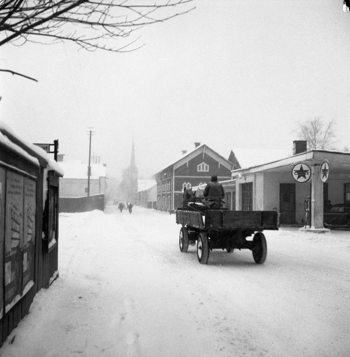 Östra Hamngatan i snöfall. En man kör med häst och kärra förbi Texacos bensinstation. På höger sida ses hamnmagasin. I bakgrunden kan man skönja Heliga Trefaldighetskyrkan.