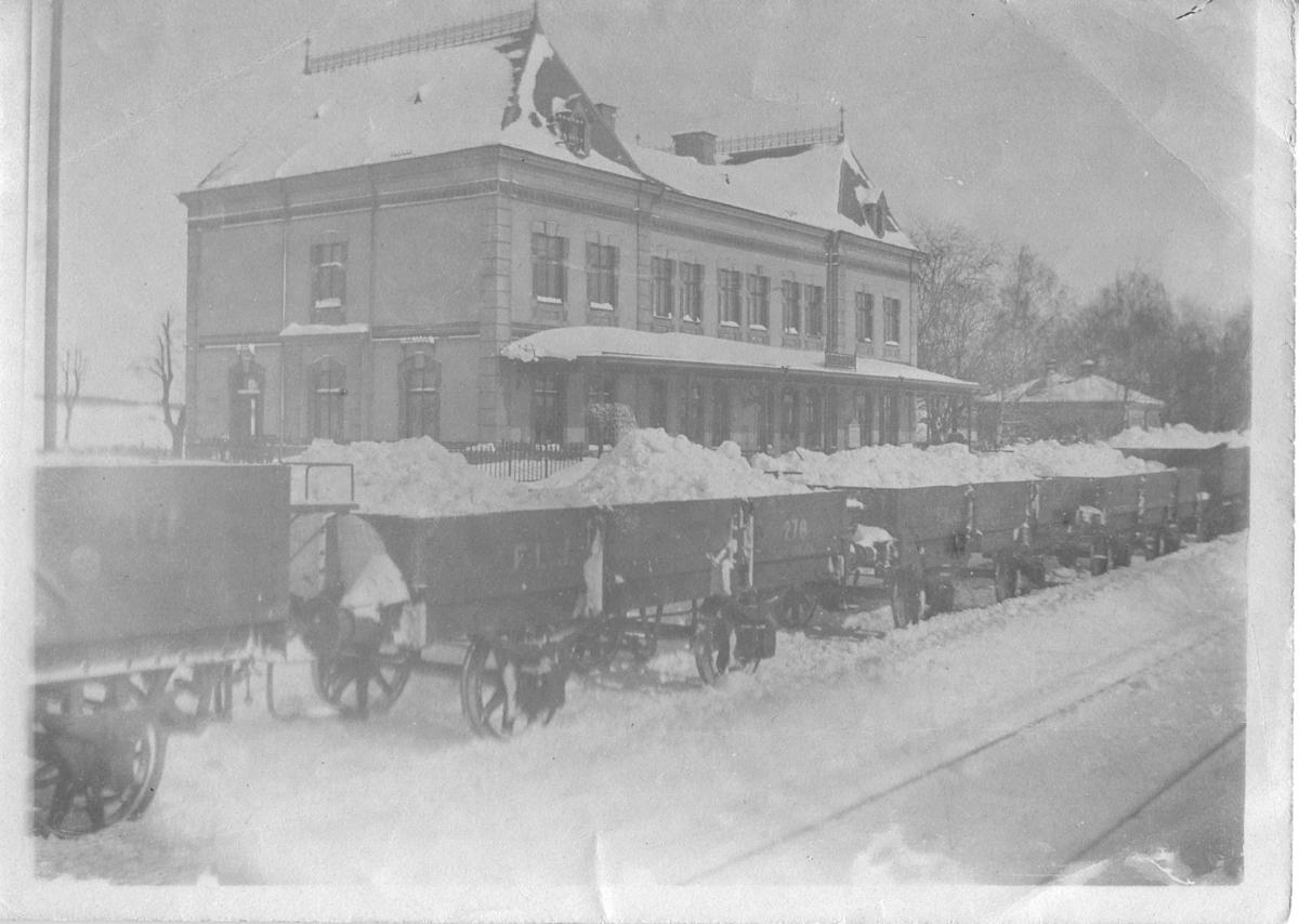Järnvägsstationen vid Köpingsvägen. Vinter. Järnvägsvagnar lastade med snö.