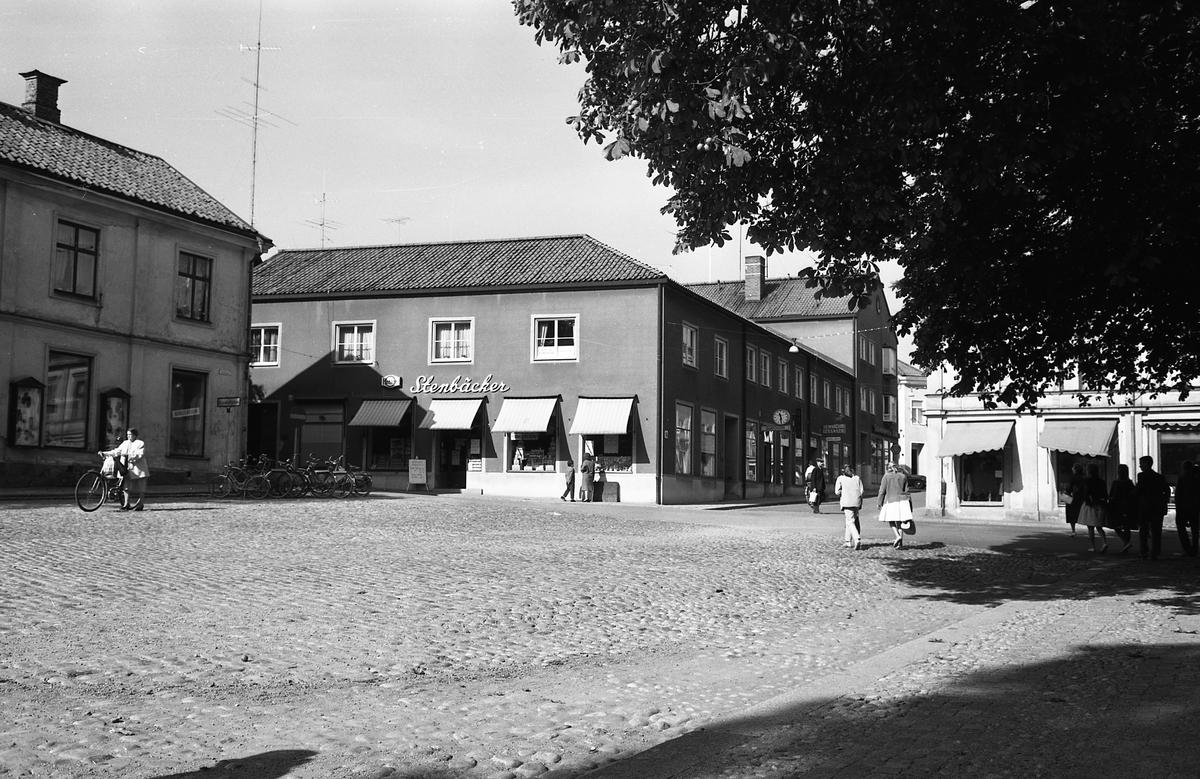 """Järntorget. Stenbäckers affär på Smedjegatan, Hemslöjd och leksaker på Järntorgsgatan. Människor i rörelse. Fotografen har angivit att bilden ingår i """"Dokumentation av fastigheter söder och norr om ån. Bilder och beskrivningar finns på Arboga Museum""""."""