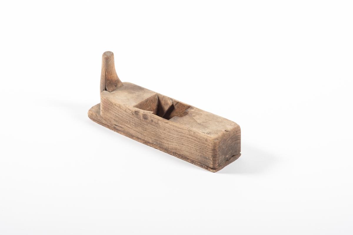 Høvelstokken er satt sammen av et tykt trestykke og en tynn fjøl som danner undersiden. Foran på høvelstokken er det et håndtak, formet som et horn. Håndtaket er festet med en skrue. Trekilen som skal holde jernet på plass i høvelstokken mangler.
