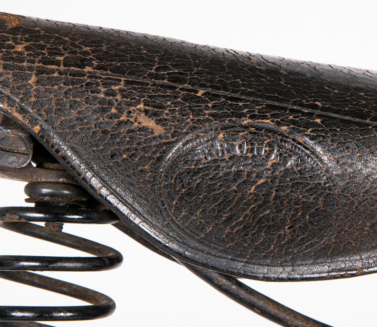 Velociped, Froms tillverkning. Cyckel med svart lack och linjerad gulddekor. Lädersadel av märket Brooks. Text på ramen: FROM [H]ERKULES. Serienummer på styret: 460. Handtag av svarmålat trä. Handbroms fram.
