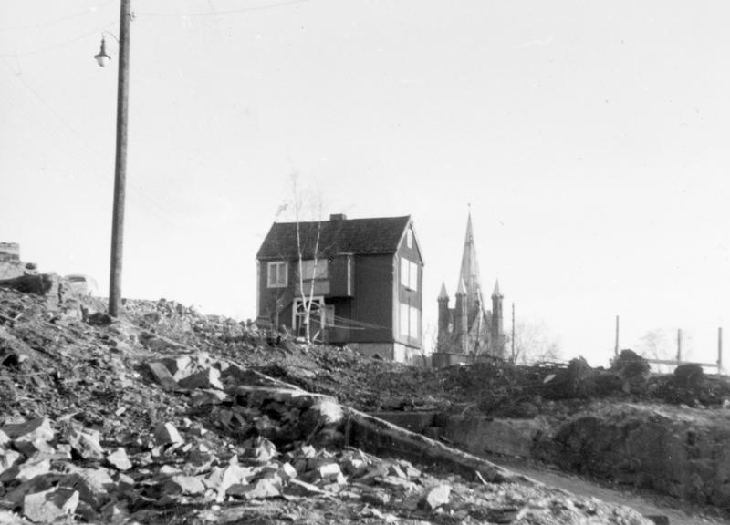 Vi flyttet fra Langleiken til Stupingata i 1958. Det var stor lykke da vi kom dit hvor det var innlagt vann, men fortsatt utedo. Det var ikke mange hus igjen rundt oss. Da de rev uthuset til nabohuset, rev de også veggen til vår utedo, så vi fikk utsikt ned til Grønland. Da fant de ut at de like godt kunne rive resten av uthuset vårt også. Så sto vi da der uten do. Etterhvert fikk vi ny vedbod og do. Bildet er tatt våren 1960/61.