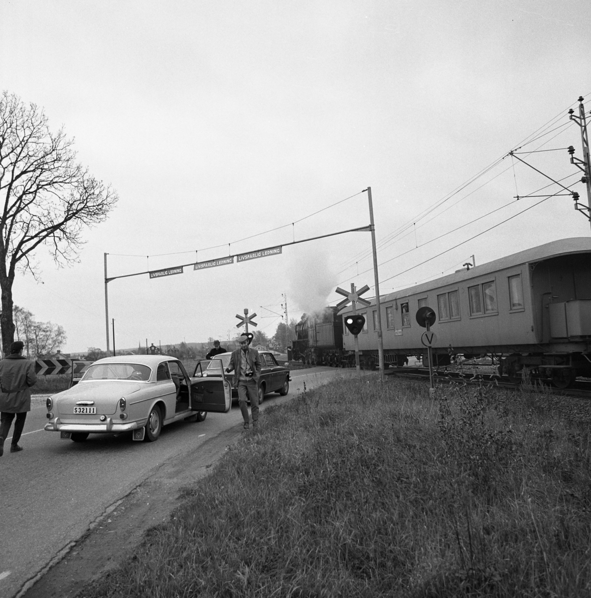 Ånglok vid järnvägsövergången vid Emaus. Två bilar väntar. Man med kamera.