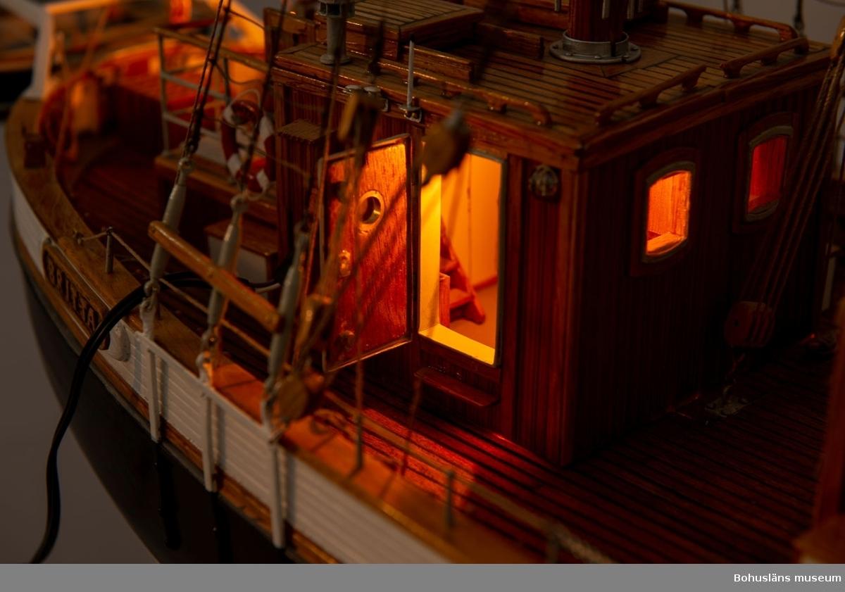 Modell av skolfatyget T/S BRITTA. Uddevallas skolfartyg. Skala 1:25. Tillverkad i samma material som originalet med ek i köl, spant, bordläggning, garnering och reling. Lärk i däckshus, master och bommar. Gran i gafflar och toppstång. Furu i däck. Modellen är inredd, har demonterbart däckshus, rörliga delar såsom rigg, dörrar, luckor, peke, toppstång och är försedd med utvändig och invändig belysning. Stativ med mässingsplakett. Modellen kan lyftas med hjälp av en sinnrik och enkel lyftanordning Gösta Nilsson har utvecklat.