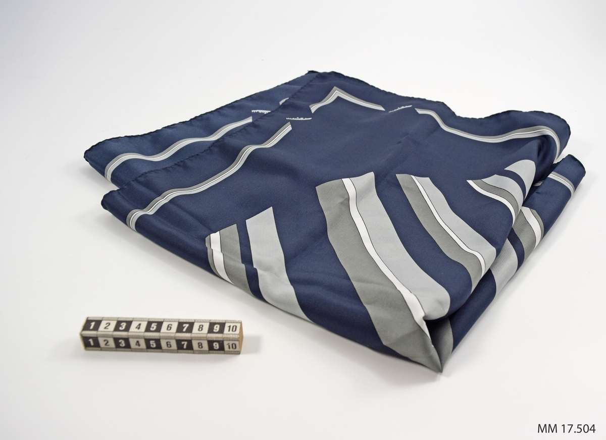 Marinblå scarf med tryckt mönster, grå och vita diagonalt ställda breda ränder lagda i cirkelformat mönster i mitten. Längs kanten rand avbruten på båda sidor om varje hörn av små fartyg, kustkorvett typ Stockholm. I ena hörnan vit etikett, angivande kvalitet och tvättråd.