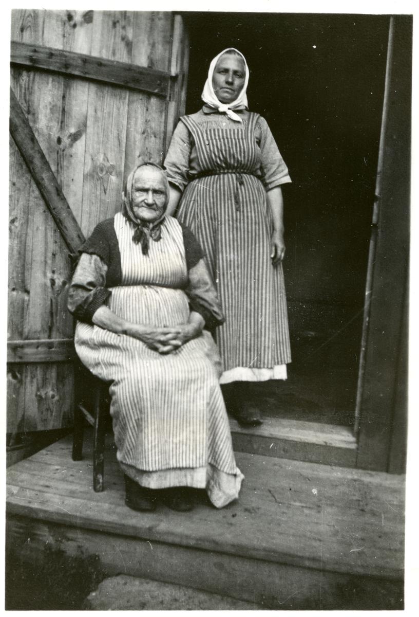 """Dingtuna sn, Västerås. Stockkumla gård. Två kvinnor med randiga förkläden och """"hucklen"""".  1898-1910."""