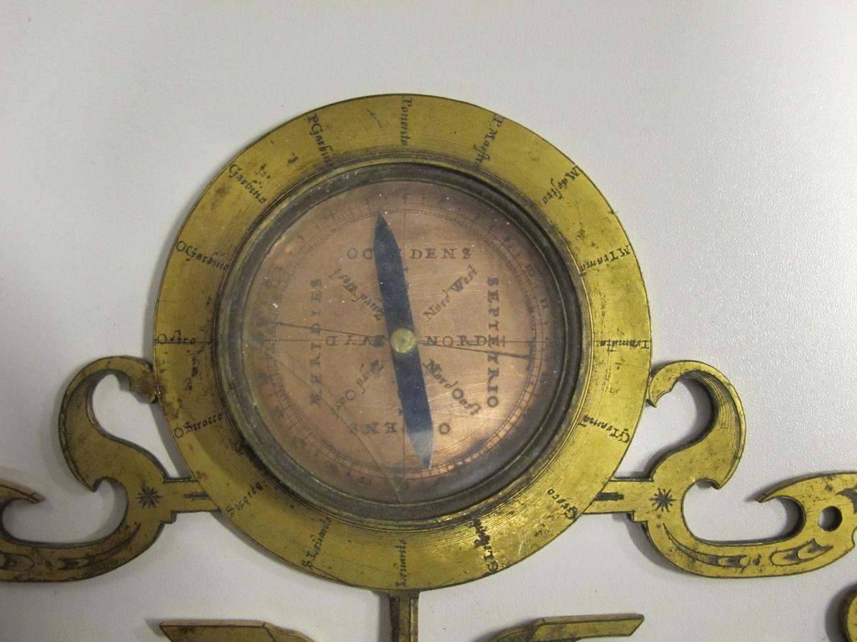 Diopterlinjal av förgylld koppar med bredvidliggande kompass i koppar. Italiensk och delvis holländsk text på linjalen med siktdiopter och likformig skala med 120 enheter.