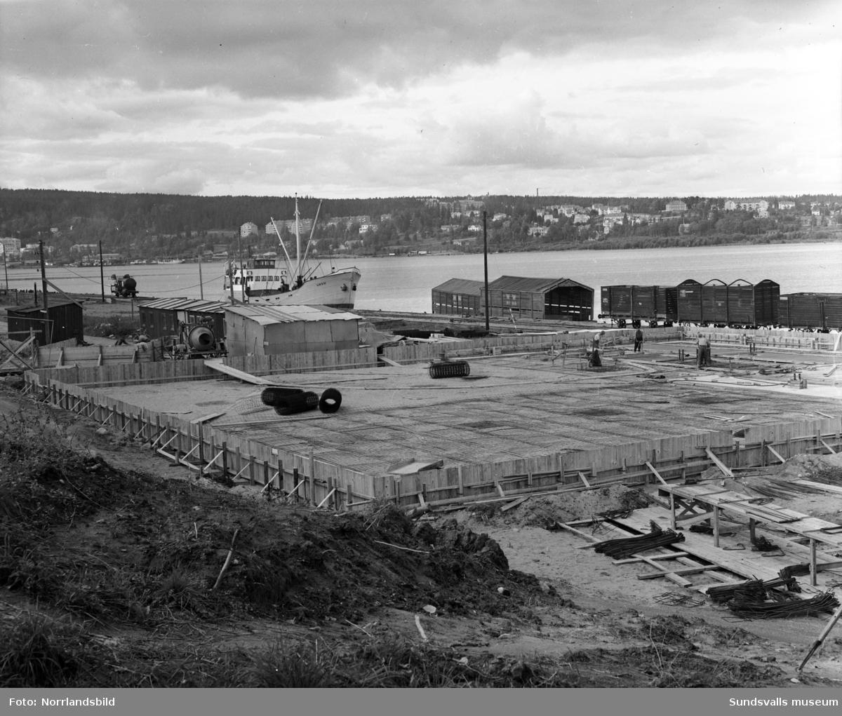 En ny magasinsbyggnad byggs vid Mokajen. Bakom syns Mons strömmingssalteri och längre bort oljehamnen. I högerkant gammal bebyggelse i Skönsmon.