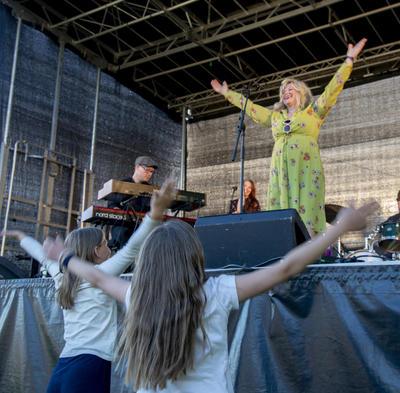 Mocci Ryen står på scenen og rekker armene i været, unge jenter i publikum står foran scenen og gjør det samme.