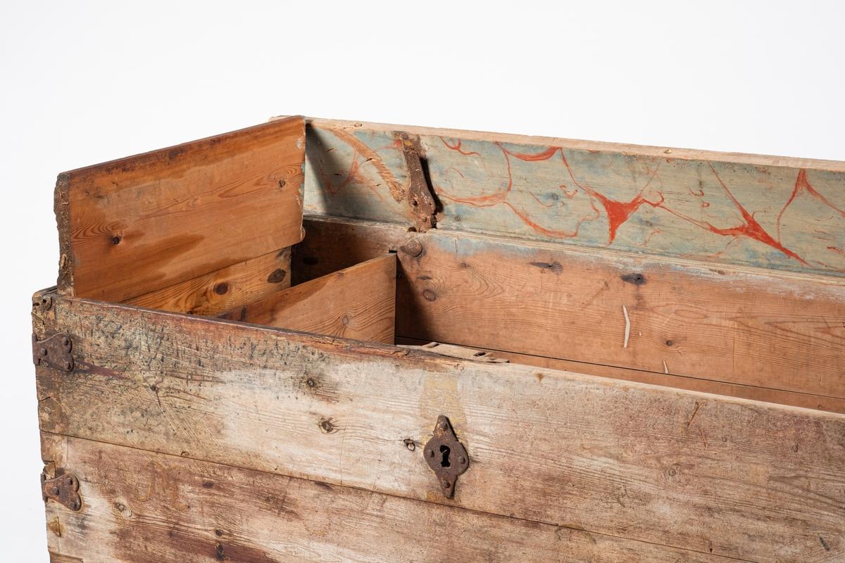 Jernhåndtakene er vridde, beslagene er hjerteformete, og treverket er malt i marmormønster. Noen av treplankene er profilerte.