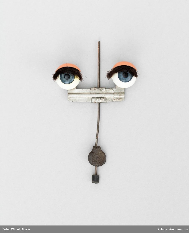 KLM 28082:213 Dockögon, i ställning av metall. Ställning: metallstav, tunn av stål, nertill på staven, en tyngd, av bly, pendylformad, I mitten på staven, två smala metallister vågrätt sammanfogade, med ett docköga fäst på vardera sida. Öga, rund glob, av plast, vit med blå iris och svart pupill. Ögonlock, av metall, hudfärgat, ljust, med ögonfransar under, av hår, täta, svarta, limmade ovanpå ögongloben.