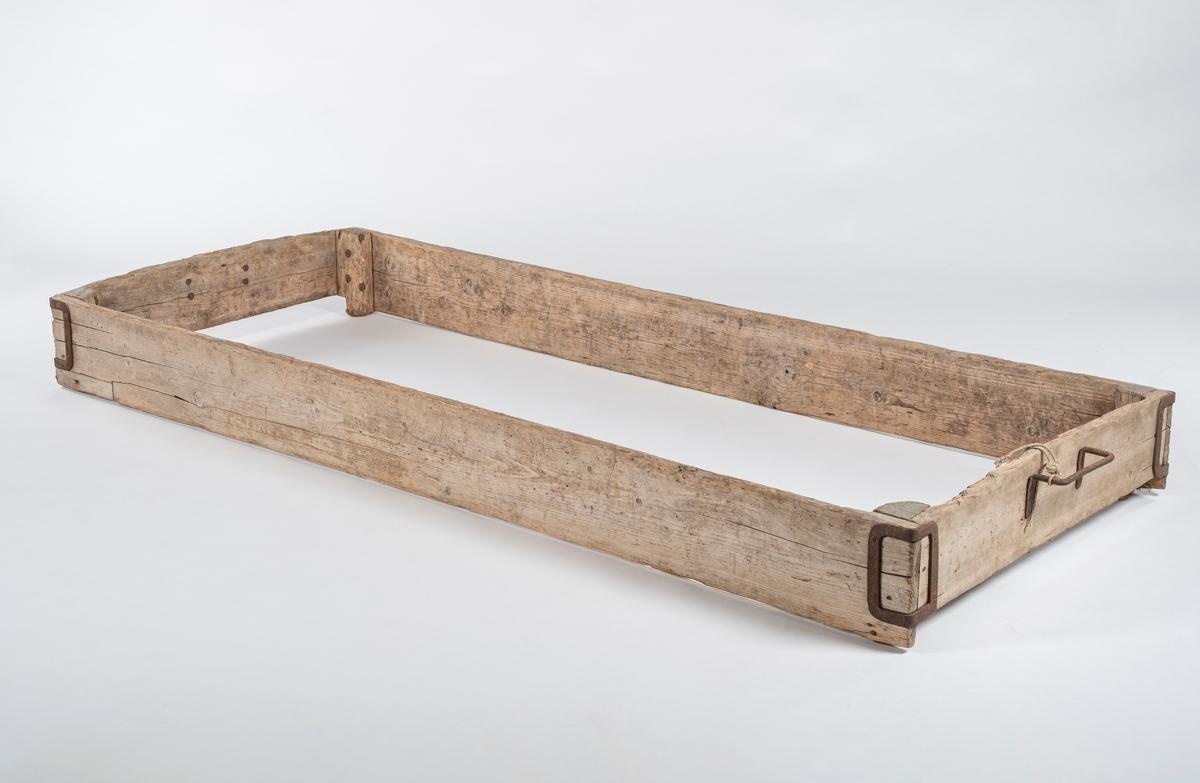 Karmen består av fire bord og fire hjørneklosser på innsiden. Det er håndtak i hver ende. Hjørnene på karmen har beslag av jern. Det er malingsrester i det ene hjørnet.