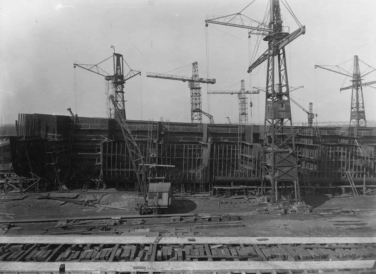 Motivet viser MT SPINANGER (bygget i 1927) under bygging ved Schiechau i Gdansk. 6 store havnekraner rundt skroget som ligger i tørrdokk.
