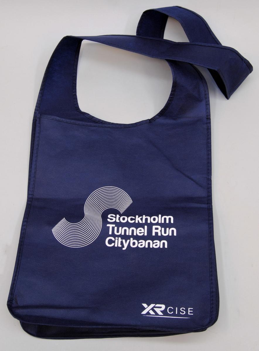 """Mörkblå axelväska av 100 % polypropylen. På framsidan finns texten: """"Stockholm Tunnel Run"""", tryckt i vitt. Längst ned i vänster hörn finns märkningen: """"XRCISE"""", tryckt i vitt. I väskan finns en svart textillapp med tvättråd."""