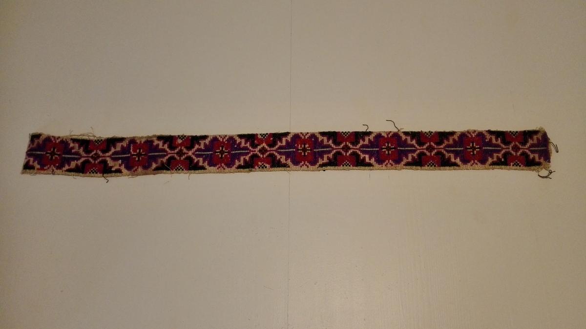 1 belte  Belte sydd på kretong av blå, lila, grönt og brunt ullgarn. Uten spenner. Længde og bredde 68 og 5 cm. Neppe meget gammel.  Kjöpt av Trina Strandos, Lavik ved Bendik Avedal, Lavik.