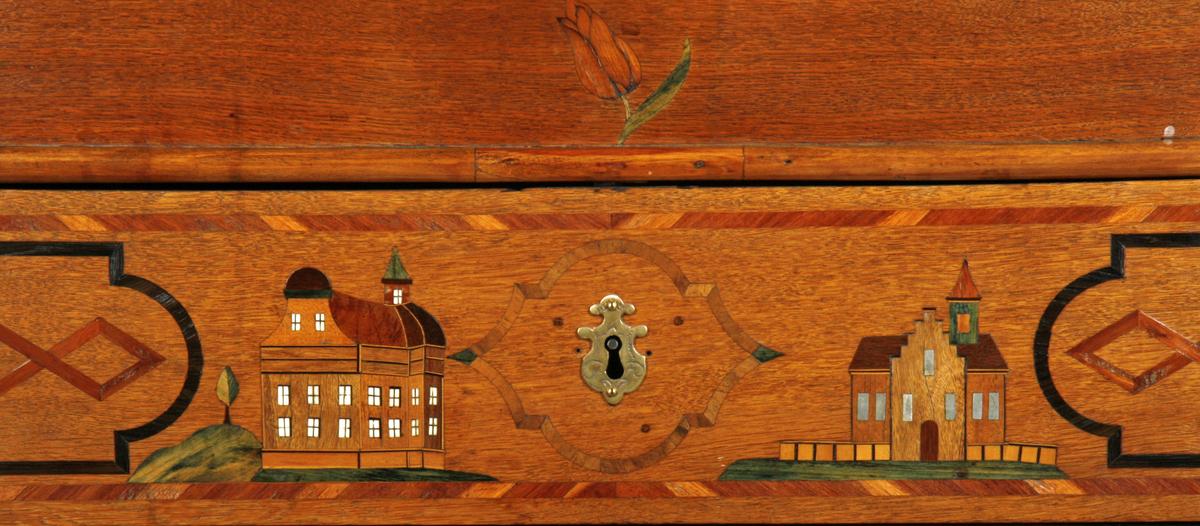 Skatollet er utført i eik og innlagt med forskjellige sorter naturlig farget tre, samt innfarget treverk og tinn og ben. Nederst har skatollet profilert fotlist over fire konsollføtter. Skatollet er delt mellom de to nederste skuffene og den øverste. Uttrekkslister på sidene til støtte for den nedfellbare skriveklaffen. På toppflaten er to stjerner i intarsia, skriveklaffens fyllinger har motiv av to vaser med tre blomster i hver, omgitt av firkantet ramme i båndintarsia. De to nederste skuffene er dekorert med to fugler på gren, mens den øverste skuffen har to hus. Det ene huset har vinduer innlagt med ben, mens det andre huset har tinninnlagte vinduer. Skuffene har en bred stripe intarsia langs kanten. Ytters på hver side av skuffene finnes to geometriske figurer, den ene utenfor den annen i bånd formet intarsia i lyst og mørkt tre. Blindfeltet over skuffene er dekorert med to stjerner og en tulipan i midten. Sideflatene er dekorert med to enkle figurer i båndformet intarsia, det samme motivet finnes også som ramme om nøkkelhullet på skuffene. Innenfor skriveklaffen finner vi i midten et lite skap, døren er dekorert med en stjerne innenfor en rektangulær ramme som er knekket og buet øverst. På hver side av skapet er en skuff og over dissse to åpne rom. Under skapet og delvis inder skuffene finnes et åpent rom med løs planke over. Ytterst på begge sider er fire avtrappede skuffer. Alle skuffene har en intarsia langs kanten.