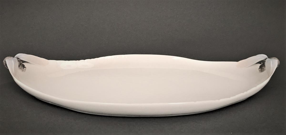 Avlangt ellipseformet fat. Hankene er utformet som libeller. Langs kanten er det fremstilt margeritter i lavt relieff.