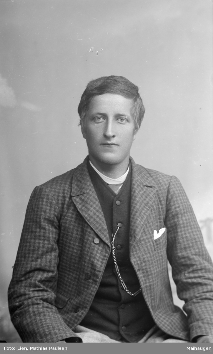 Portrett av yngre mann i rutet jakke og mørk vest