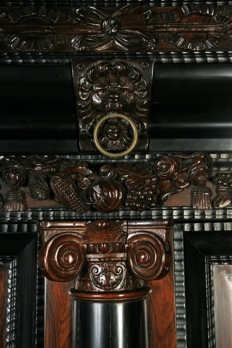 Jakaranda (?) finér, ibenholt, to dører med fyllinger og tre glatte søyler i fronten, skuff nedentil metallring i gesimsen.