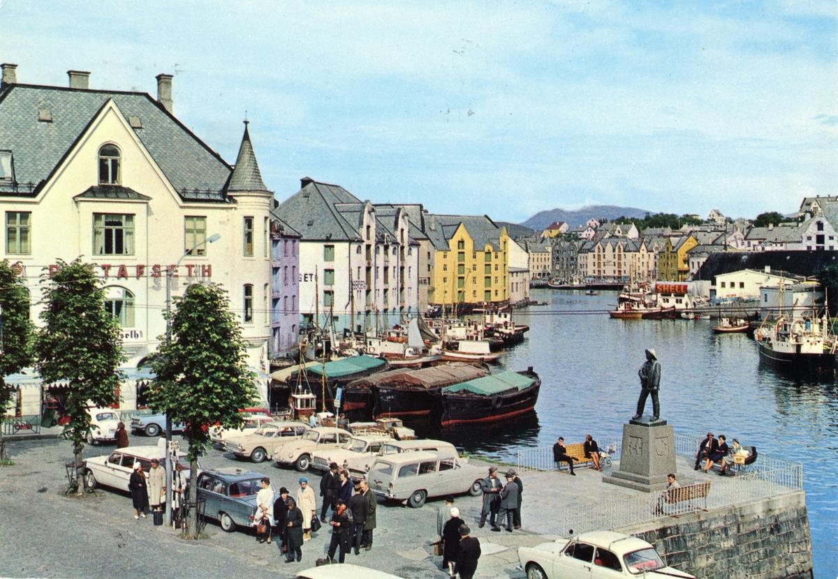 Oversiktsbilde av Brusundet i Ålesund, med Apotekertorget og statuen i forgrunnen. Flere biler er parkert på torget.