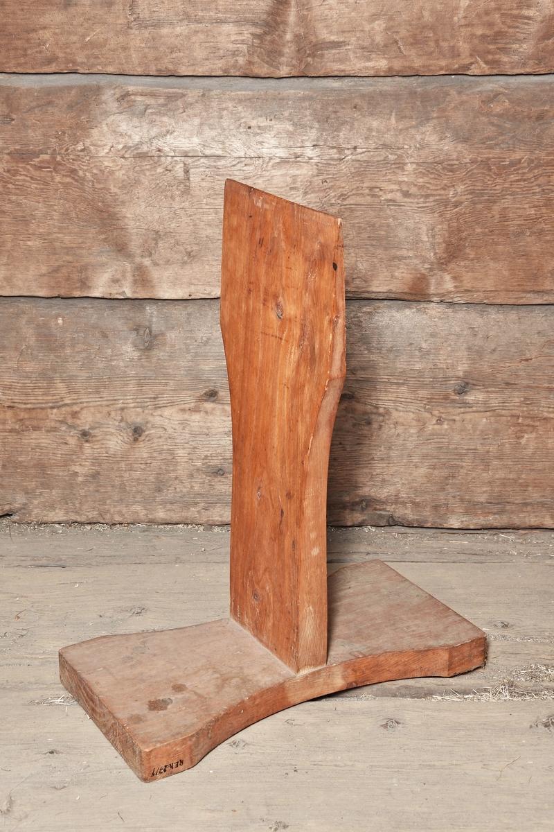 Skäktstol av trä. Rektangulär bottenplatta något insvängd. Från plattan utgår i vinkel en rakt uppstående bräda, avsmalnande upptill.