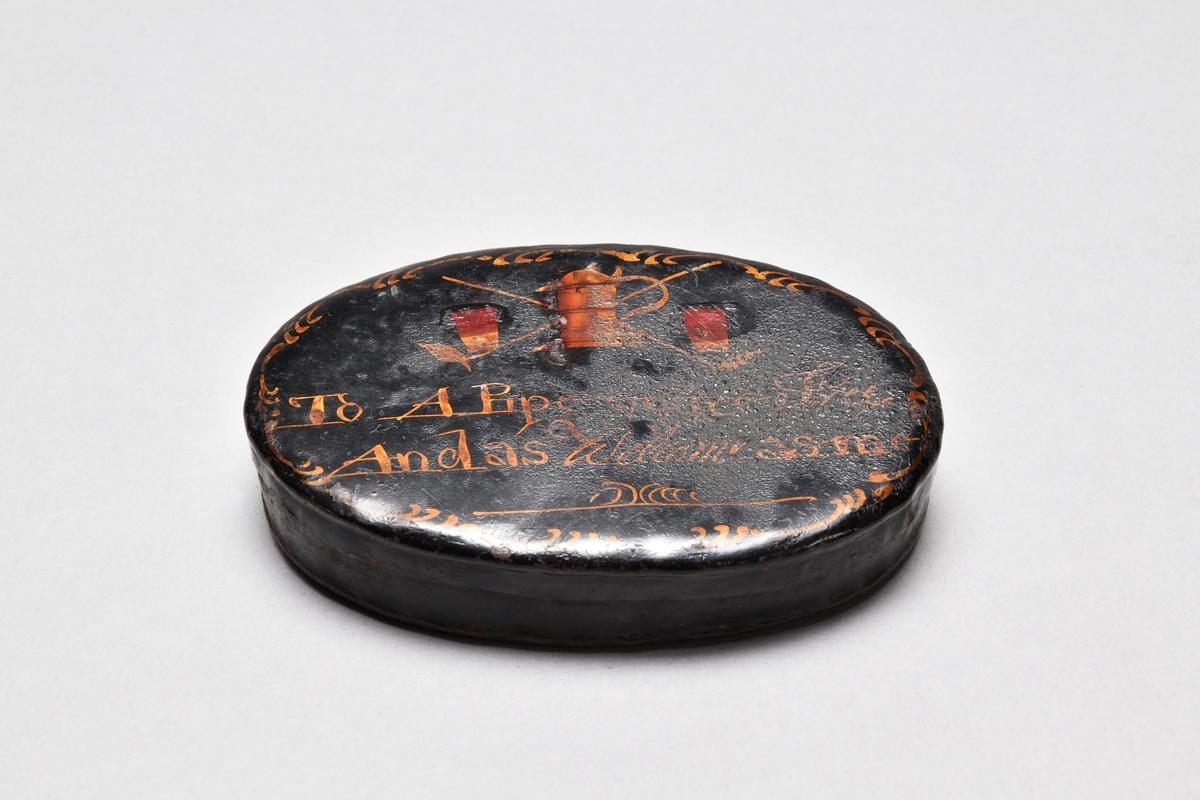 Tobaksdosa av järnplåt, oval, med tättsittande lock. Svartlackerad. Dekor i gulrött i form av 2 korslagda långpipor, ett stop och 2 dricksglas samt bård i gyllengult.