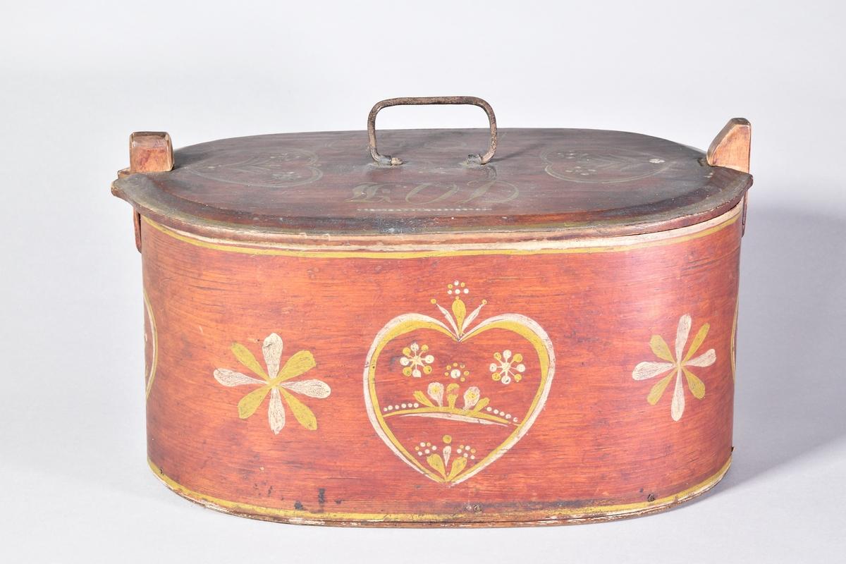 """Mössask i form av en äska, svept av furuspån, oval, målad med rödbrun bets med dekor. Svepändarna fastsydda med efterstygn och kedjestygn, yttersta svepänden med dekorerat avslut. Utanpåliggande botten, hopsatt med träplugg. Lock med järnhandtag, märkt """"KOD / 1859"""". Två ståndare för lockets låsning. Den målade dekoren i vitt och gult; hjärtan och enkla blommor."""