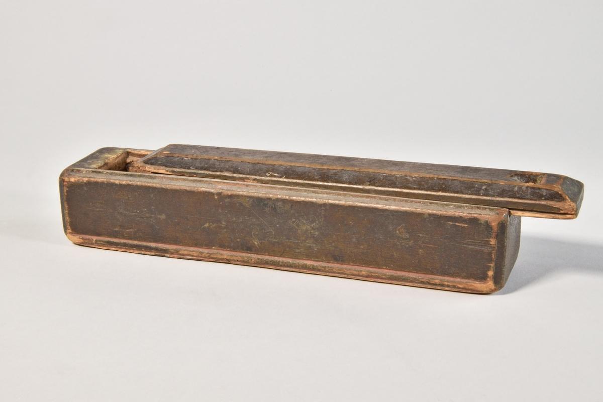 Rektangulär låda av furu, med skjutlock. Ursprungligen grönmålad. Lätt profilerade kanter med rester av bemålning i rött. Lockets sidor fasade, tumgrepp.