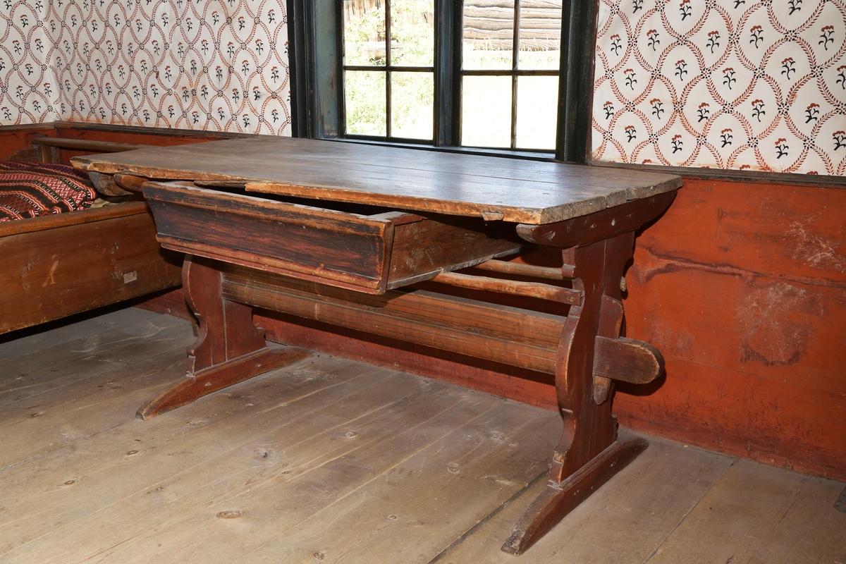 Bordsunderrede av furu, rödmålat, profilerat bockställ, rak kraftig bom. En bordslåda ligger lös på två smala slåar som är spikade på bockarnas sidor. (Skivan har ursprungligen inte tillhört bordet.)