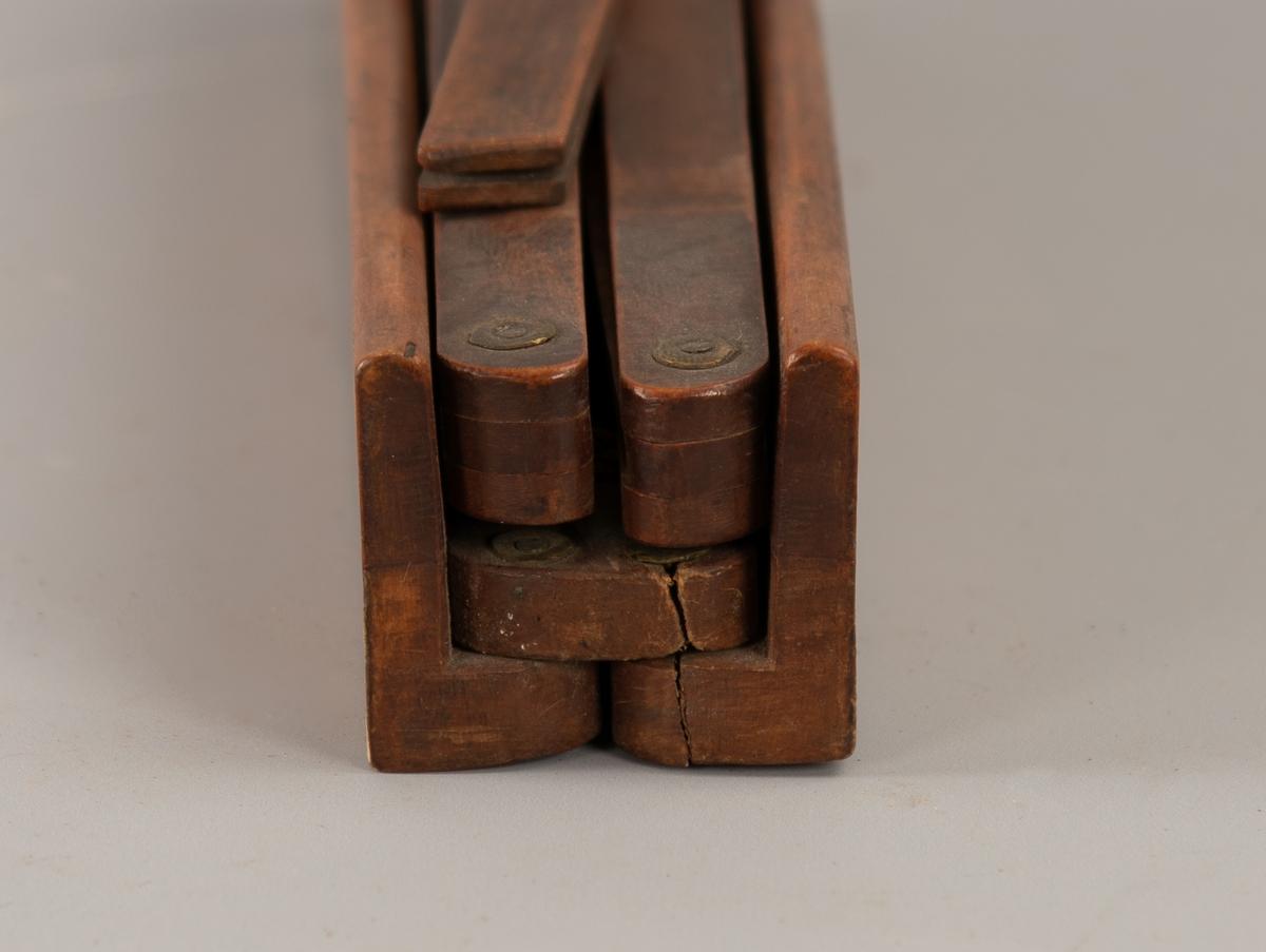 Hylse, lang og smal, med et flatt trestykke i, som er festet med to messingskruer i den ene ende. Fra denne kan det slås opp en liten stav med en  spiss tapp. I den ende som ikke er festet, kan slås ut to  lange trespiler, den ene med to sammenfoldbare spiler ytterst,  den andre med tre spiler ytterst. Den ene av spilene har streker og  tall (overstrøket) med tusj.