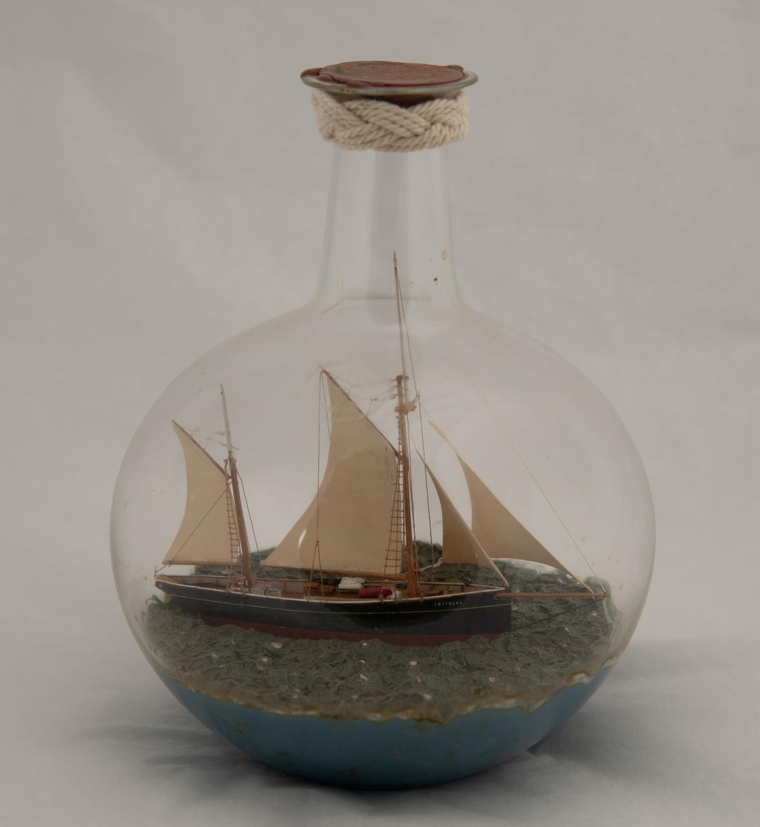 """Flaskeskute: """"Ekstrand"""" , galeasrigget kutter , før ombyggingen i 1990.  Kuleformet flaske av klart glass . Sortmalt skrog , rød under vannlinjen , hvit kant , hvite seil. Lys blågrønn kruset sjø."""