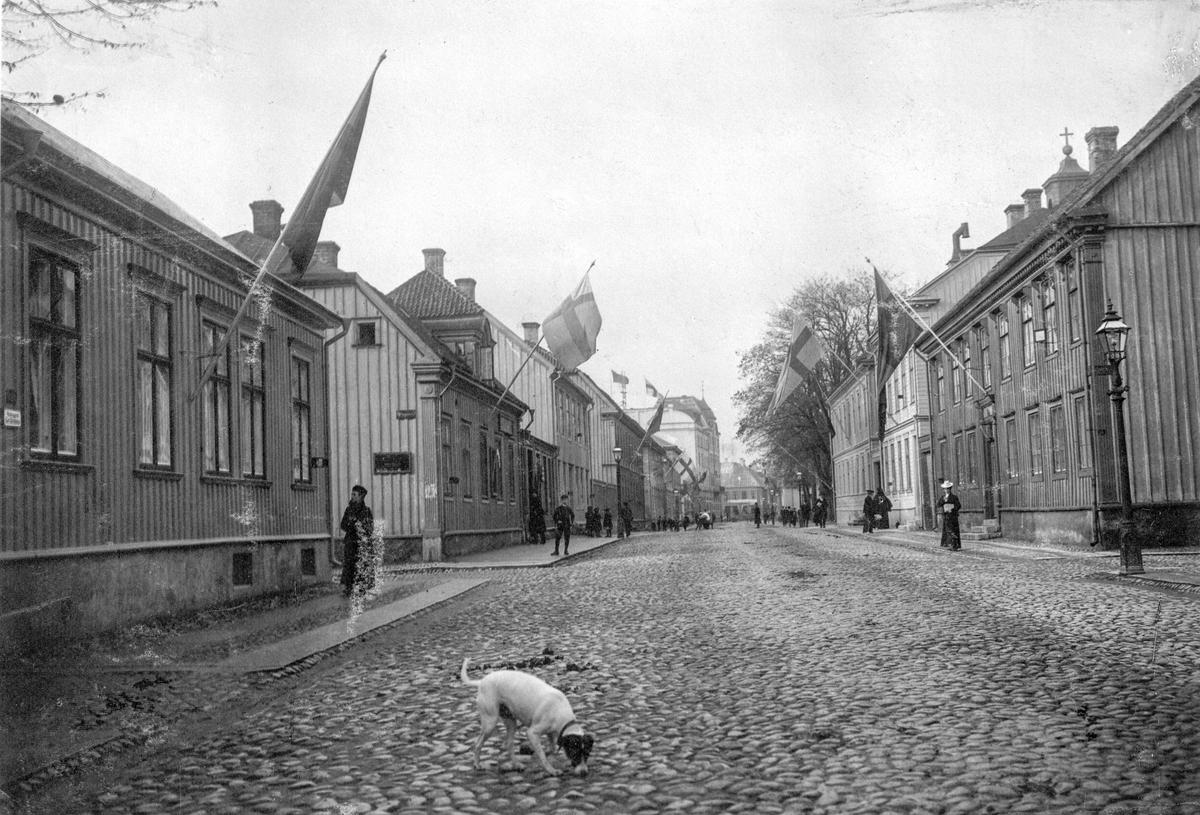 Östra Storgatan mot väster 1 november 1906 då svenska flaggan för första gången hissades efter det att unionen med Norge upphört och unionsmärket tagits bort. Närmast till vänster Östra Storgatan 62 och Björngränd. Intill de stora träden till höger ligger Kristine kyrka ocoh längst bort anas Hovrättstorgets byggnader.