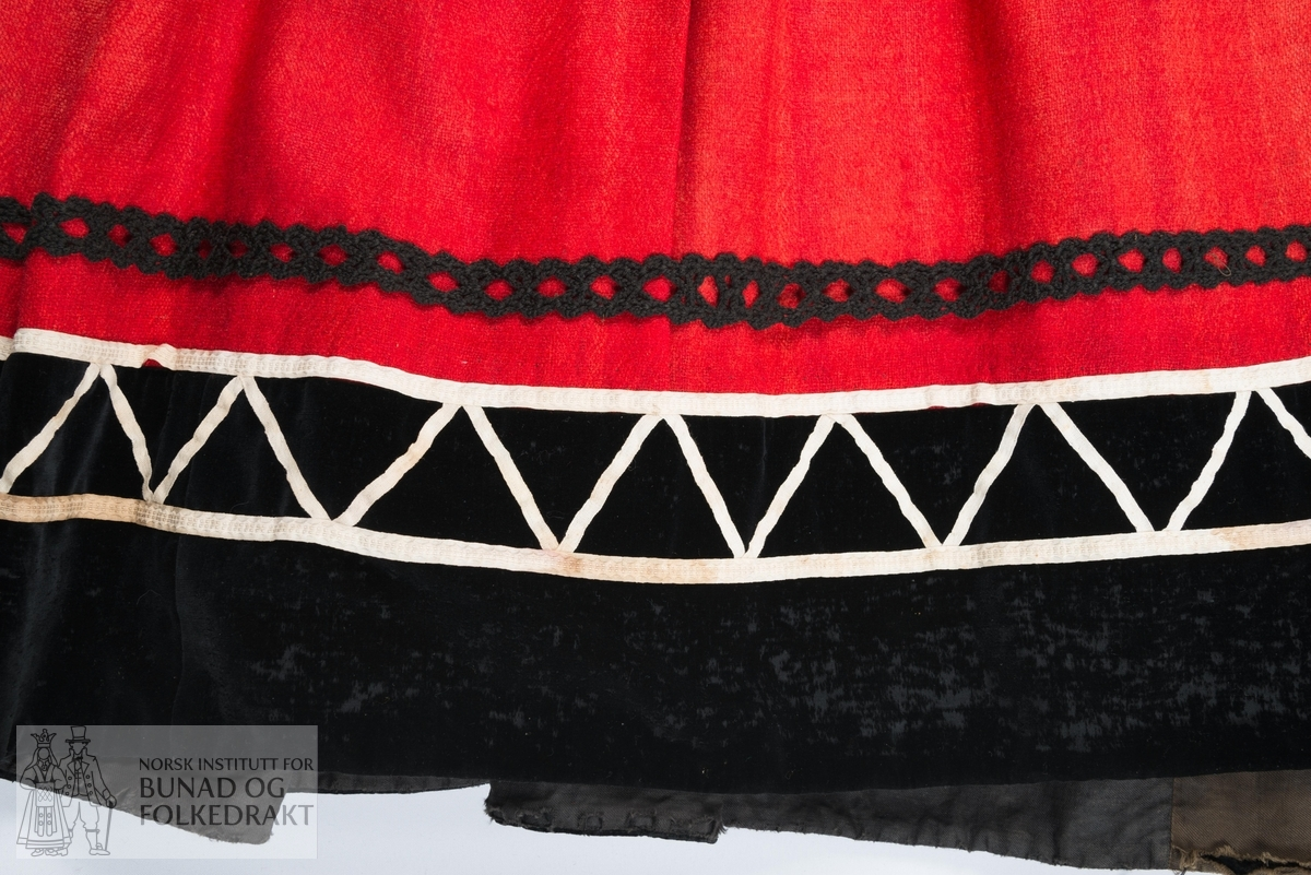 Stakk. Tidligere understakk tatt i bruk som Jonsokbrudestakk. Stakk av rød ull, kanskje hjemmevevd. Nederst er den kantet med et bredt felt, svart bomullsfløyel som er dekorert med hvite bomullsbånd lagt i sikksakk-mønster.  Over dette en smalere, svart heklet kant, av ullgarn. Stakken er lagt i legg til linningen med et glatt parti midt foran. Linningen er av rødt bomullslerret. Til linningen er det festet trykknapper og hekter som kan brukes til å hekte den til trøya i registrering 0061.  Det er festet to brede strikker til linningen med sikkerhetsnåler, disse er nyere og har blitt brukt  som skulderstropper for å holde stakken oppe. Lukkes med en hekte på brukers venstre side. Maskinsøm med noe håndsøm.