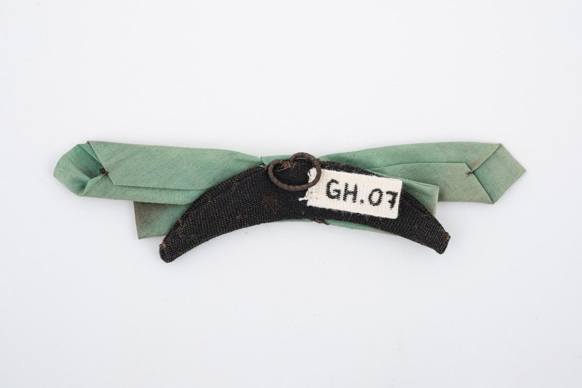 Sløyfe av tekstil i lys grønn farge. Den er sydd på en buet stiv plate, trukket med sort tøy. På platen er det en hempe.