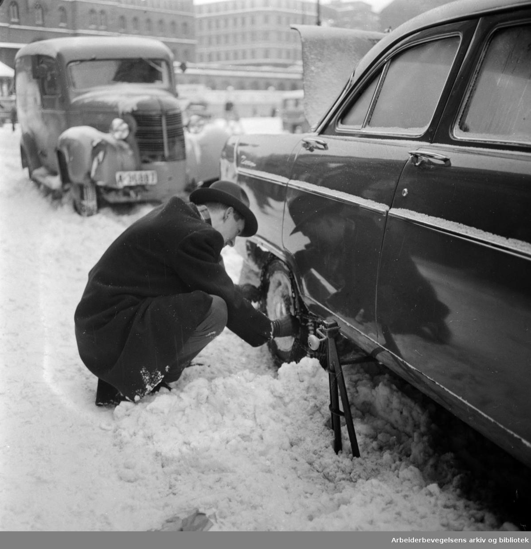 Uventet kraftig snøfall i Oslos gater. Montering av kjettinger. 1. Mars 1960.