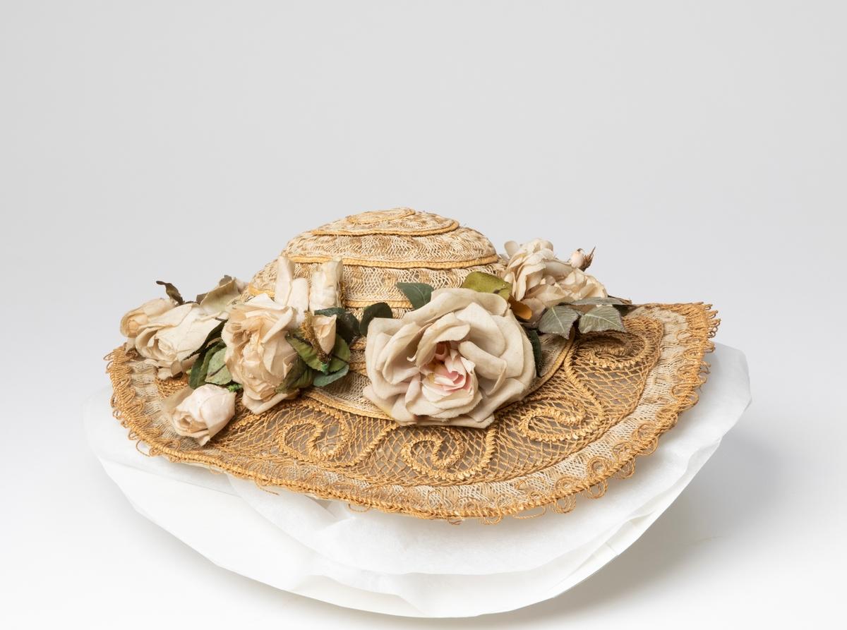Stråhatt för dam i gyllene strå, snöre och snodd flätat och mönstrat i olika modeller. Undersidan är klädd i tunnt tyg mönstrat med blommor/fjärilar. Hatten är garnerad med tygrosor.