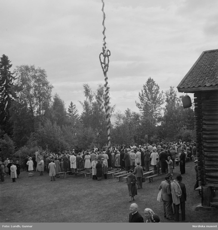 """Motiv: (ingen anteckning) ; Kvinnor och män i folkdräkt dansar vid en midsommarstång inför en publik vid midsommarfirande, tre hästskulpturer 2Jemt-Olofs hästar"""" (träsnidaren Jemt Olov Persson), porträtt av en man som står vid en husvägg, porträtt av en kvinna som står på en balkong."""