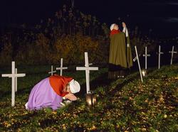 Sørgende kvinner blant hvite kors på kaupangens kirkegård.