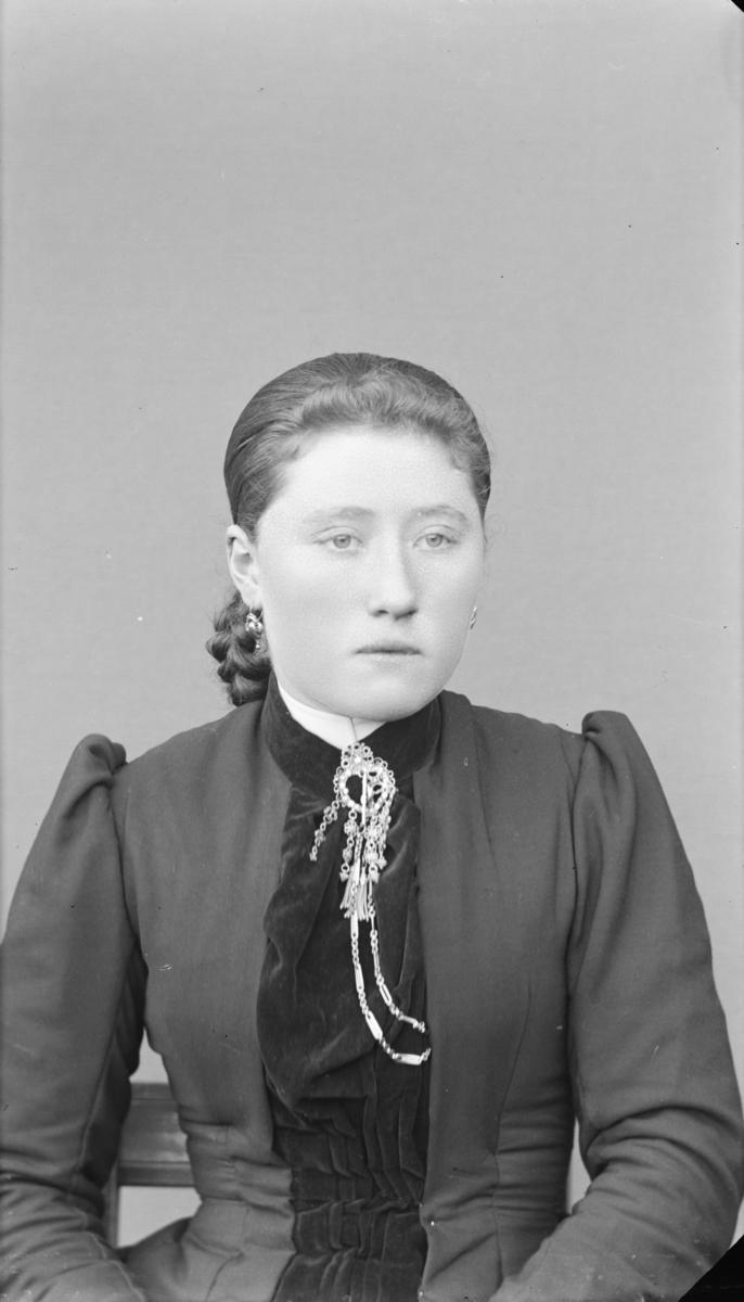 Portrett av kvinne med glatt hår og øredobber, kledd i kjole med puffermer og halssølje