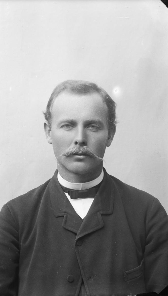 Portrett av mann  med bart, kledd i kvit sjorte med sløyfe og mørk jakke