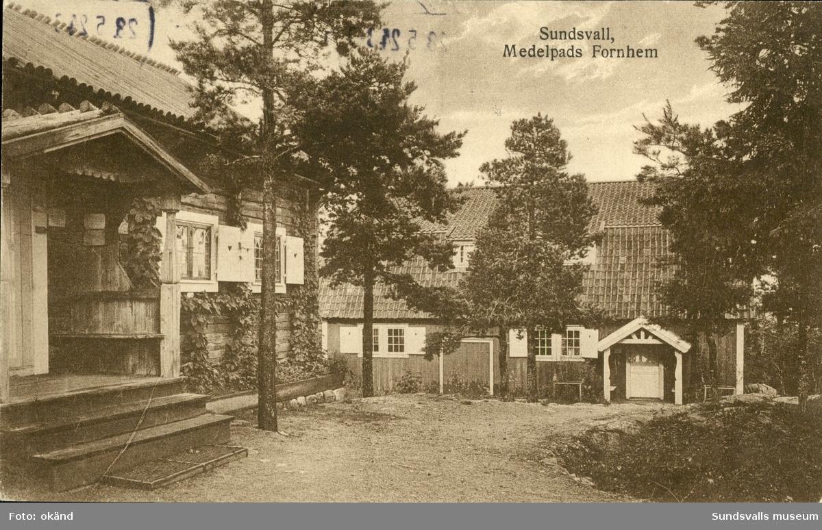 Vykort med motiv över Bredsjöstugan och trampmangeln på Norra Stadsberget i Sundsvall med texten: Medelpads Fornminnesförening.